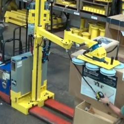 Mobile lift with adjustable height boom for reaching into racks.